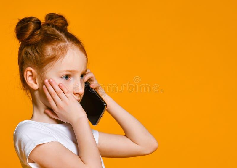 Ni?a emocional bonita que habla por el tel?fono m?vil fotos de archivo