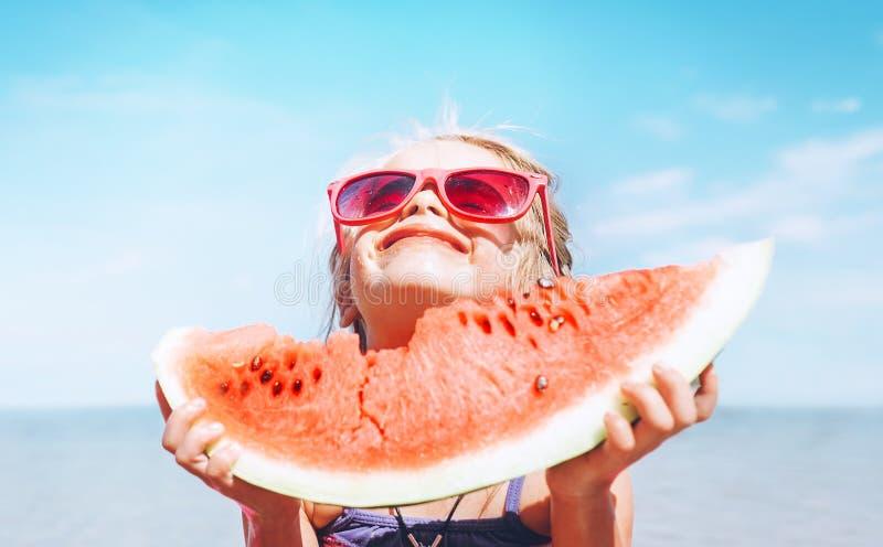 Ni?a en gafas de sol rosadas con el retrato divertido del segmento grande de la sand?a Imagen sana del concepto de la consumici?n imagenes de archivo