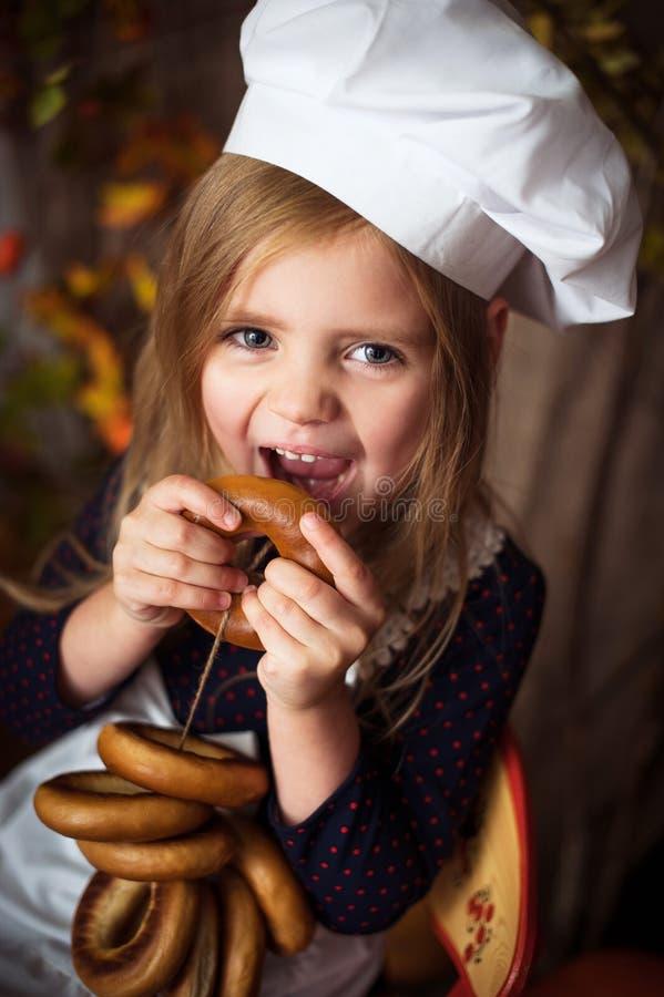 Ni?a en ropa del cocinero con los panecillos en sus manos y sonrisa imagen de archivo