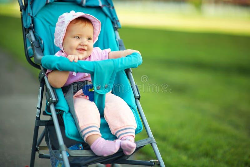 Ni?a en un cochecito beb? para un paseo en un cochecito de ni?o niño en verano al aire libre foto de archivo libre de regalías
