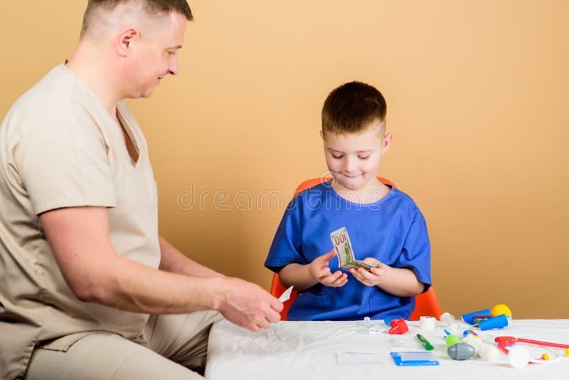Ni?ez parenting M?dico de cabecera ni?o feliz con el padre con el estetoscopio Medicina y salud padre e hijo adentro imágenes de archivo libres de regalías