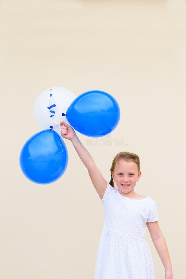 Ni?a feliz con la bandera azul y blanca de la American National Standard Israel de los globos fotografía de archivo