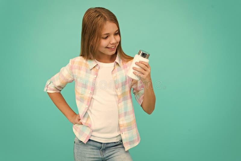 Ni?a feliz ni?o con el tarro poner crema vitaminas del control de la muchacha Belleza y moda peque?o ni?o de la muchacha con el p imagen de archivo libre de regalías