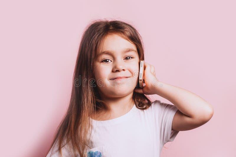 Ni?a feliz que habla en el tel?fono en fondo rosado fotos de archivo