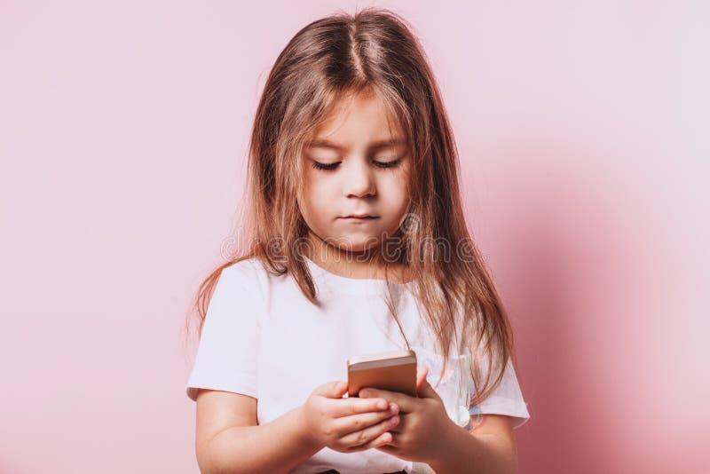 Ni?a feliz que habla en el tel?fono en fondo rosado fotografía de archivo libre de regalías