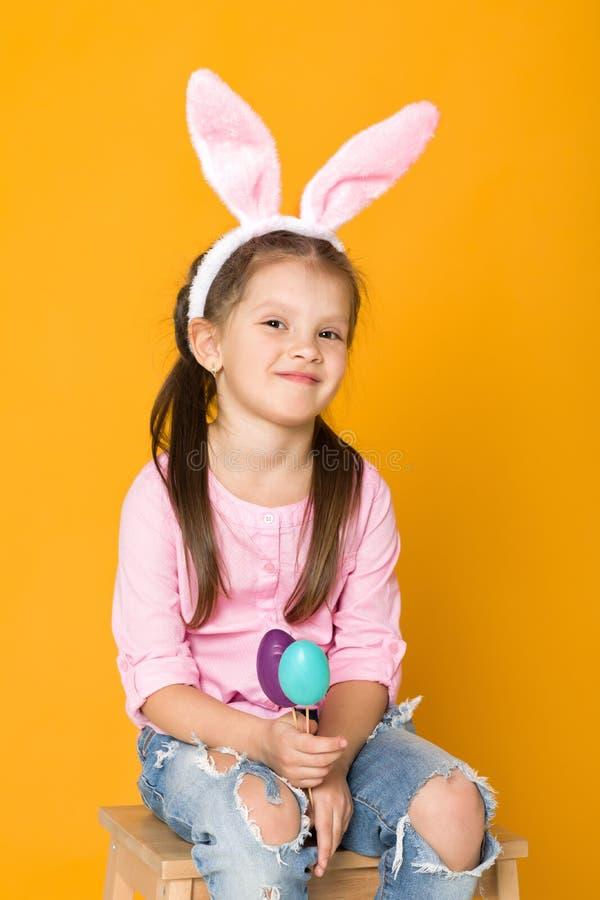 Ni?a linda con los o?dos del conejito de pascua que sostienen los huevos coloridos imágenes de archivo libres de regalías