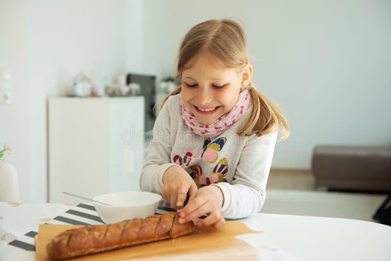 Ni?a linda que come la sopa con pan entero del grano en casa imágenes de archivo libres de regalías