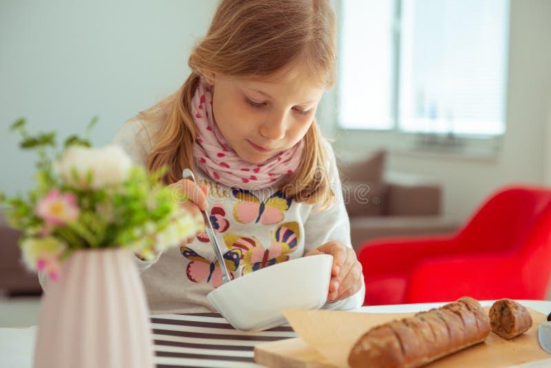 Ni?a linda que come la sopa con pan entero del grano en casa foto de archivo libre de regalías