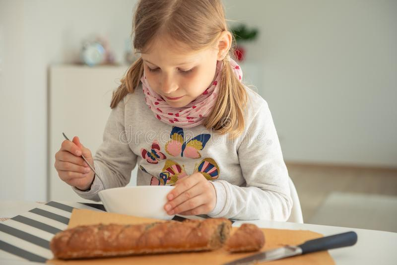 Ni?a linda que come la sopa con pan entero del grano en casa fotos de archivo