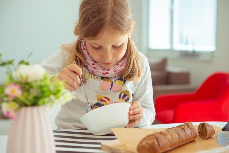 Ni?a linda que come la sopa con pan entero del grano en casa imagenes de archivo