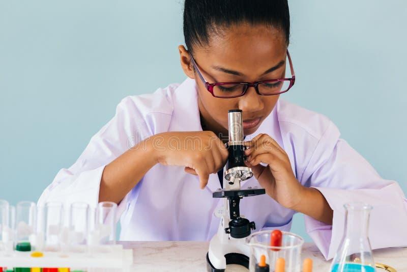 Ni?o afroamericano joven usando el microscopio en laboratorio foto de archivo libre de regalías