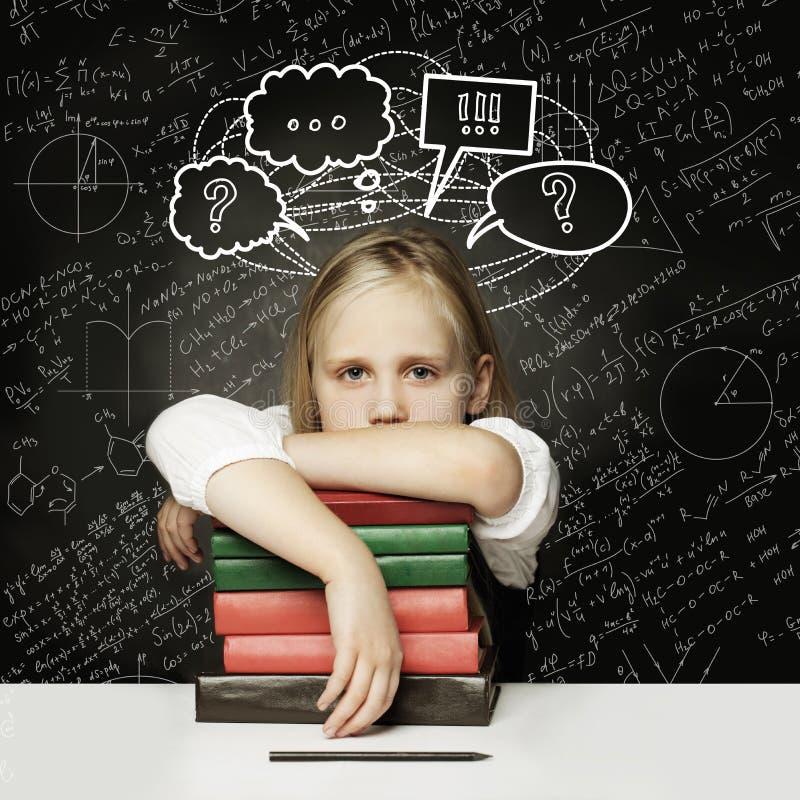 Ni?o cansado con los libros pequeño estudiante que piensa con el pulgar para arriba y las burbujas vacías de las nubes del discur fotos de archivo libres de regalías