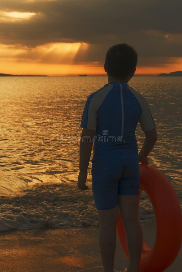 Ni?o chino con el anillo que nada el tiempo de la puesta del sol de la playa fotografía de archivo libre de regalías