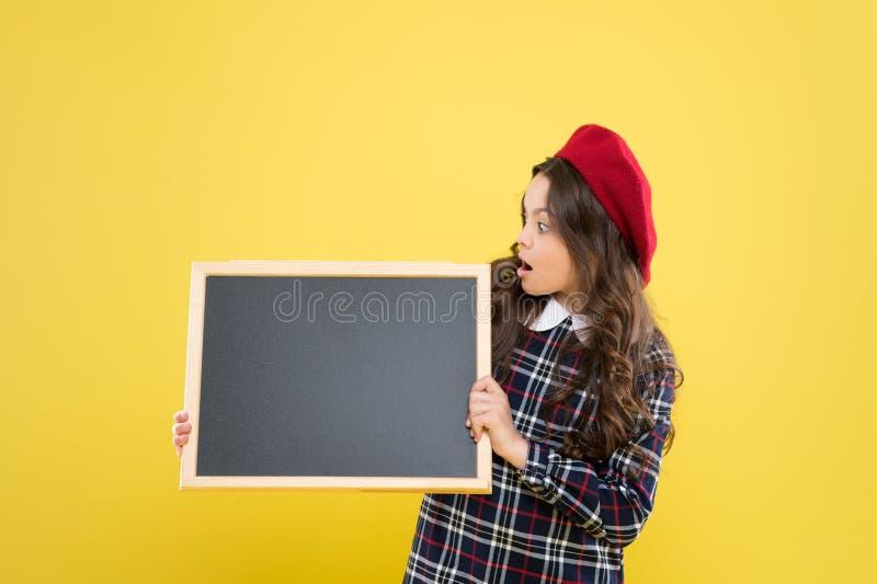 ni?o con la pizarra vac?a Aviso ni?o parisiense en espacio amarillo de la copia Muchacha feliz con el pelo rizado largo en boina fotografía de archivo libre de regalías