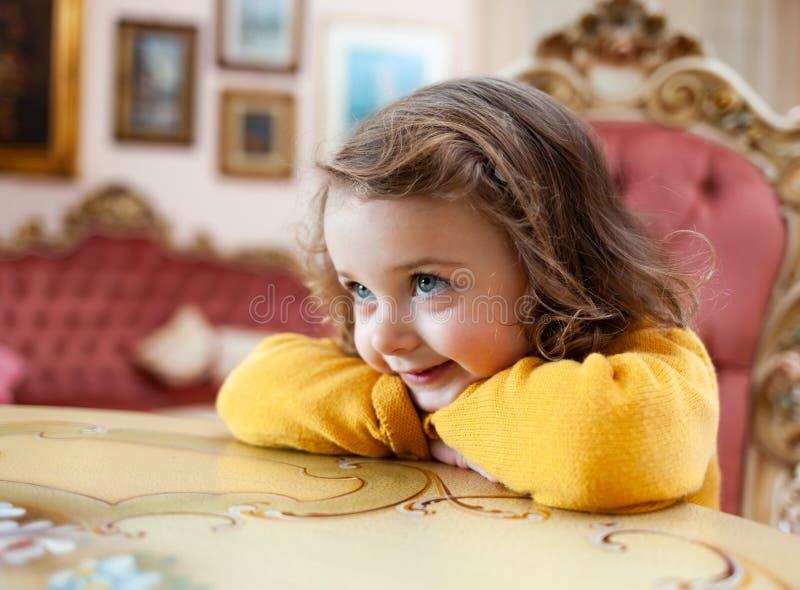 Ni?o de la muchacha en una sala de estar con la decoraci?n barroca imagen de archivo