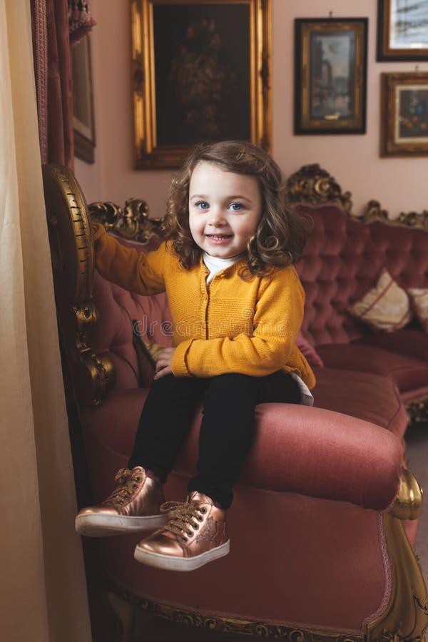 Ni?o de la muchacha en una sala de estar con la decoraci?n barroca imágenes de archivo libres de regalías