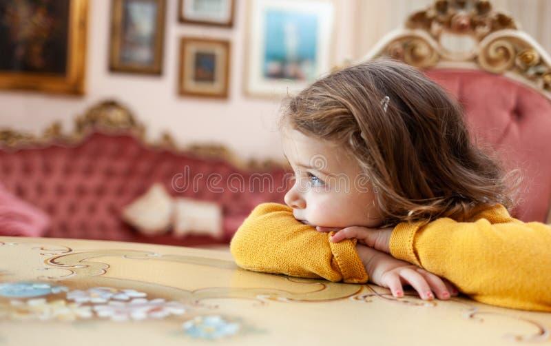 Ni?o de la muchacha en una sala de estar con la decoraci?n barroca imagen de archivo libre de regalías
