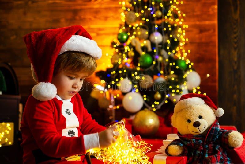 Ni?o del muchacho de Pap? Noel peque?o celebrar la Navidad en casa D?a de fiesta de la familia Juego alegre del humor del niño li fotografía de archivo libre de regalías