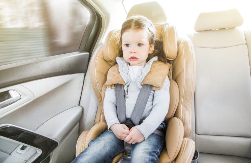 Ni?o en un asiento de carro del beb? Fijaci?n con abrazadera de Isofix asiento de carro beige en un sal?n brillante Protecci?n en fotografía de archivo