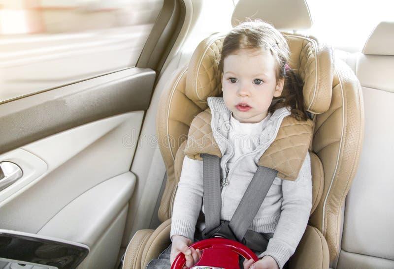 Ni?o en un asiento de carro del beb? Fijaci?n con abrazadera de Isofix asiento de carro beige en un sal?n brillante Protecci?n en imagen de archivo libre de regalías
