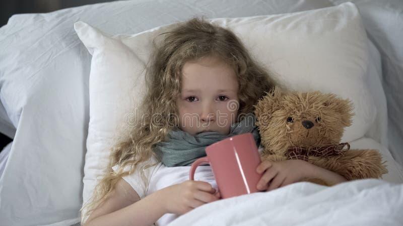 Ni?o enfermo infeliz que miente en cama con la taza de bebida caliente, gripe sufridora de la muchacha foto de archivo libre de regalías