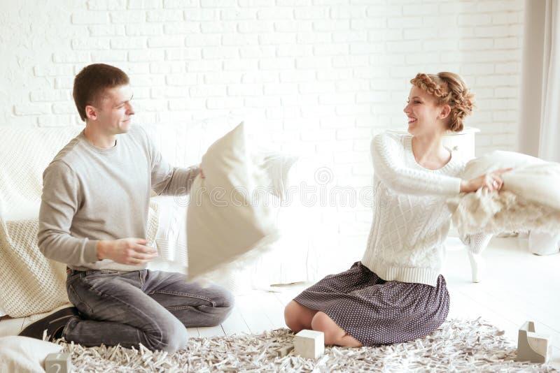 Ni?o feliz con los padres que tienen lucha de almohada en cama en casa foto de archivo libre de regalías