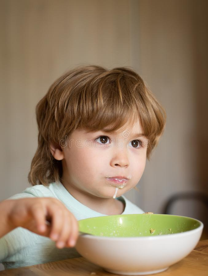 Ni?o feliz El ni?o en la cocina en la consumici?n de la tabla El peque?o beb? est? comiendo Buena mañana en familia feliz Verano fotografía de archivo