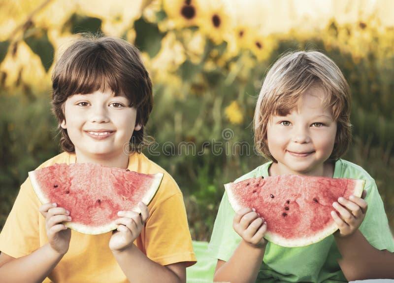 Ni?o feliz que come la sand?a en jard?n Dos muchachos con la fruta en parque fotografía de archivo