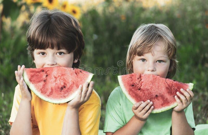 Ni?o feliz que come la sand?a en jard?n Dos muchachos con la fruta en parque imágenes de archivo libres de regalías