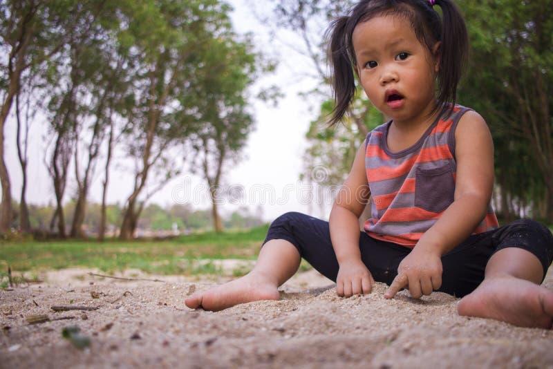 Ni?o feliz que juega con la arena, familia asi?tica divertida en un parque fotos de archivo libres de regalías