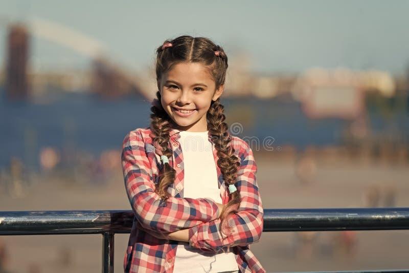 Ni?o lindo de la muchacha con las trenzas que relajan el fondo urbano defocused Organice las actividades para los adolescentes va foto de archivo libre de regalías
