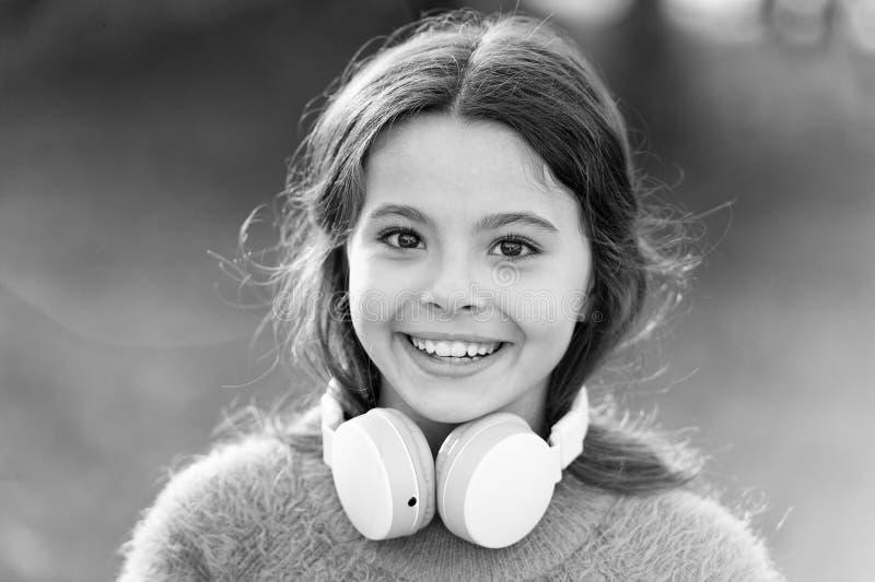 Ni?o lindo de la muchacha con los auriculares Las razones usted debe utilizar los auriculares Los auriculares cambiaron el mundo  fotografía de archivo libre de regalías