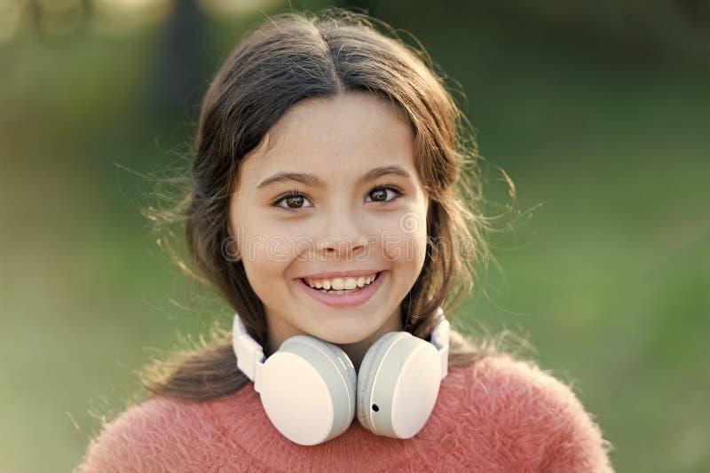 Ni?o lindo de la muchacha con los auriculares Las razones usted debe utilizar los auriculares Los auriculares cambiaron el mundo  fotografía de archivo