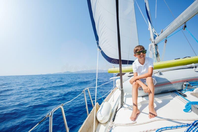 Ni?o peque?o a bordo del yate de la navegaci?n en traves?a del verano Aventura del viaje, navegando con el ni?o el vacaciones de  imagenes de archivo