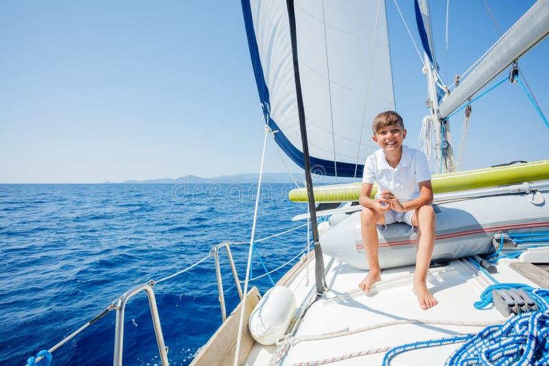Ni?o peque?o a bordo del yate de la navegaci?n en traves?a del verano Aventura del viaje, navegando con el ni?o el vacaciones de  imagen de archivo