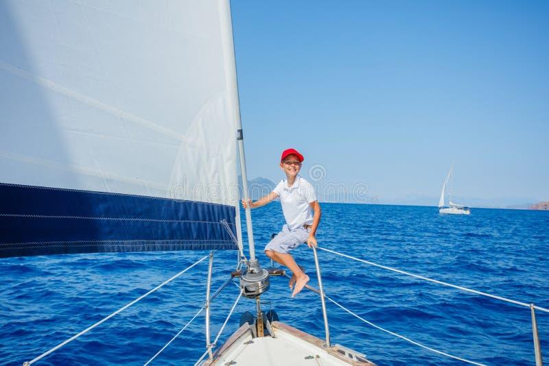 Ni?o peque?o a bordo del yate de la navegaci?n en traves?a del verano Aventura del viaje, navegando con el ni?o el vacaciones de  imagen de archivo libre de regalías