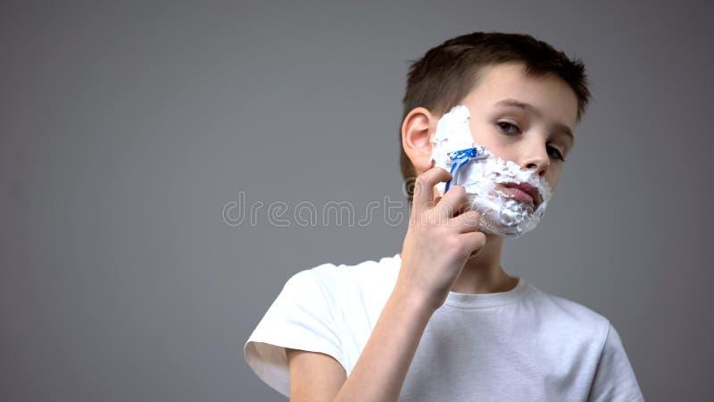 Ni?o peque?o divertido que afeita, fingiendo ser comportamiento adulto, de copiado de los padres fotos de archivo libres de regalías