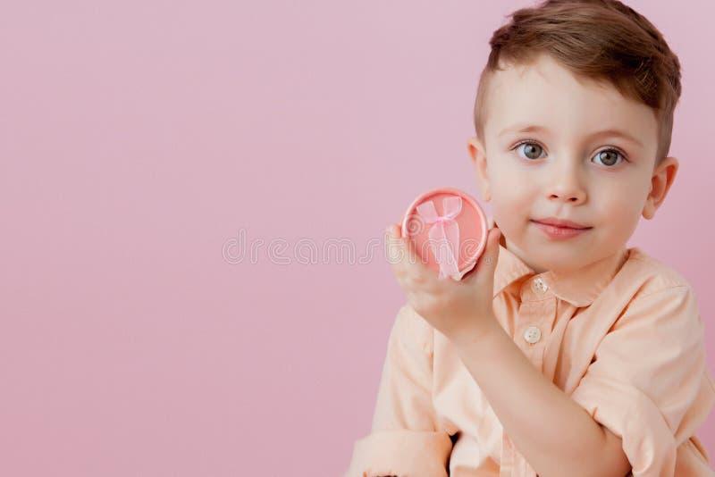 Ni?o peque?o feliz con un regalo Foto aislada en fondo rosado El muchacho sonriente sostiene la actual caja Concepto de d?as de f fotografía de archivo