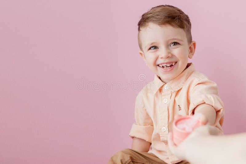 Ni?o peque?o feliz con un regalo Foto aislada en fondo rosado El muchacho sonriente sostiene la actual caja Concepto de d?as de f fotos de archivo libres de regalías