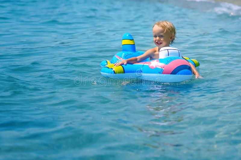 Ni?o peque?o feliz divertido lindo que juega en las ondas de agua en el oc?ano del mar en un d?a soleado imagen de archivo
