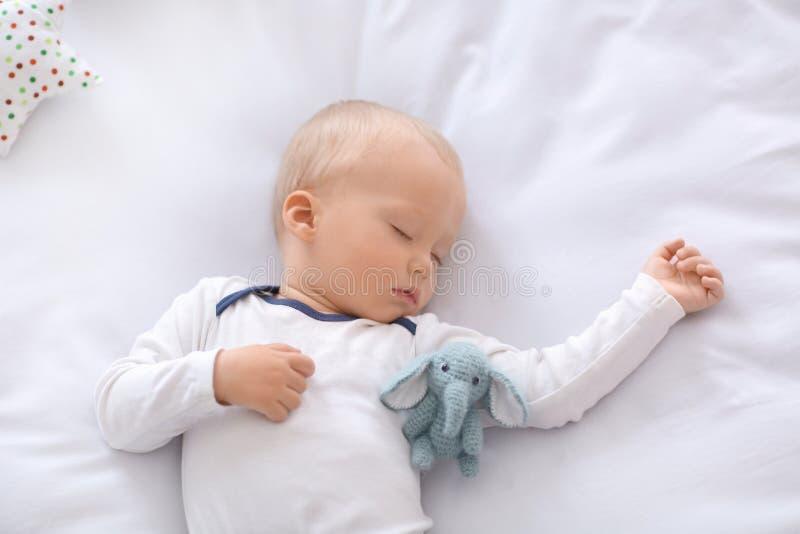 Ni?o peque?o lindo que duerme en cama fotografía de archivo libre de regalías