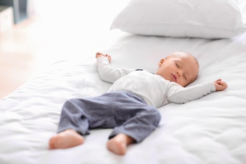 Ni?o peque?o lindo que duerme en cama imagen de archivo libre de regalías