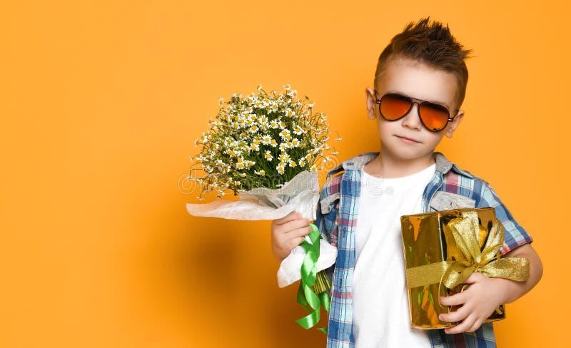 Ni?o peque?o lindo que sostiene un ramo de flores fotografía de archivo libre de regalías