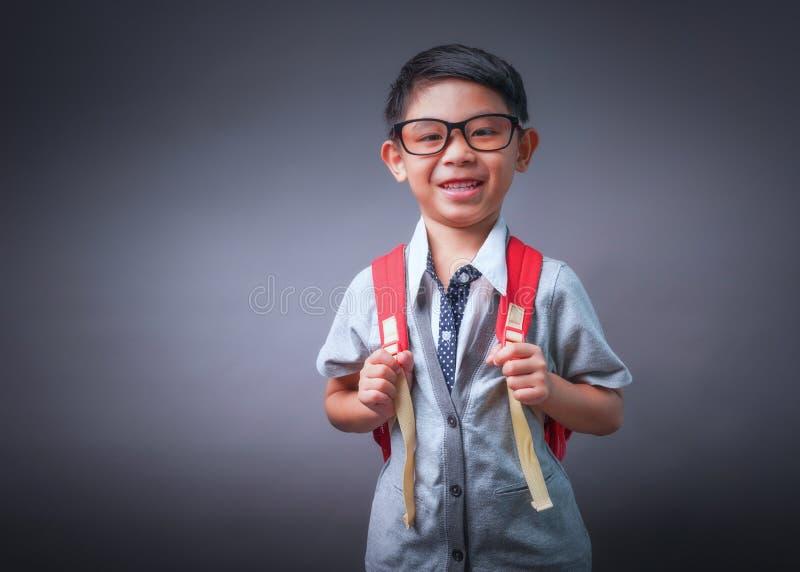 Ni?o peque?o sonriente alegre con la mochila grande mirada de la c?mara Concepto de la escuela De nuevo a escuela fotografía de archivo libre de regalías