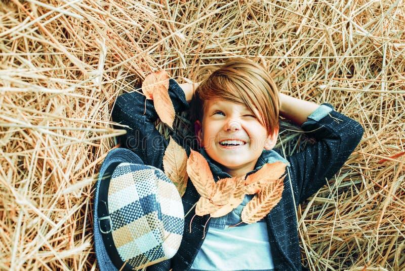 Ni?o peque?o sonriente que juega con las hojas y la mirada de la c?mara El muchacho del ni?o miente en el heno Tenencia linda del fotos de archivo libres de regalías
