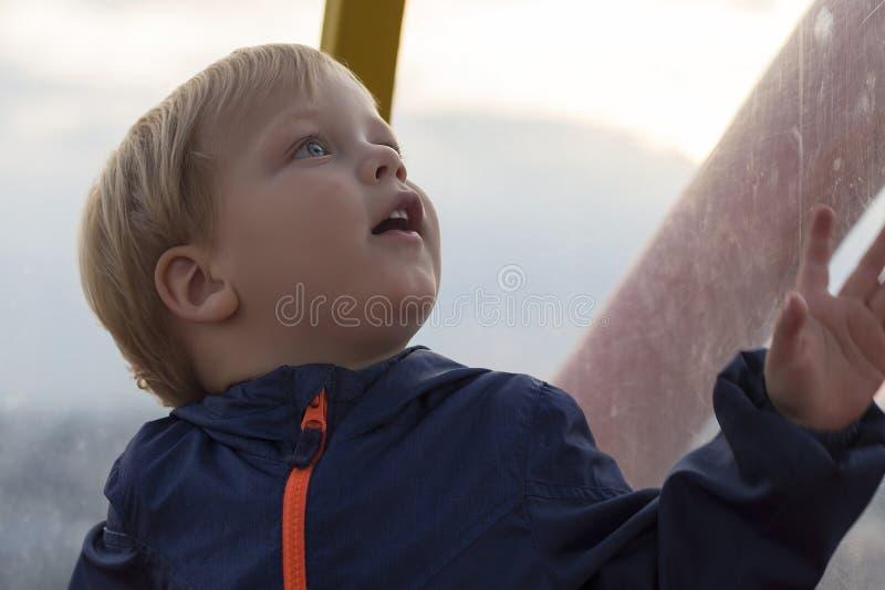 Ni?o peque?o sorprendido muy lindo Cara divertida del muchacho que mira para arriba contra fondo borroso fotos de archivo