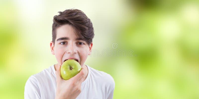 Ni?o que come la manzana verde imagen de archivo libre de regalías