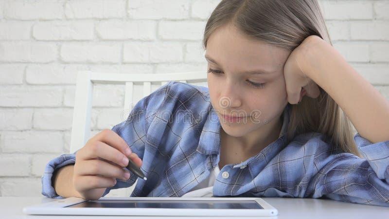 Ni?o que estudia en la tableta, muchacha que escribe en la clase de escuela, aprendiendo haciendo la preparaci?n imagen de archivo libre de regalías