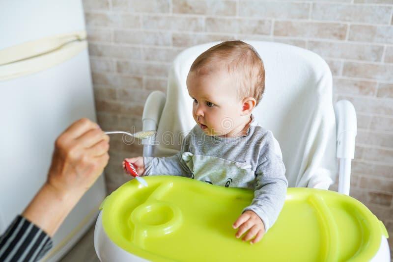 Ni?o que introduce de la madre Primera comida s?lida para el muchacho Nutrici?n sana para los ni?os foto de archivo