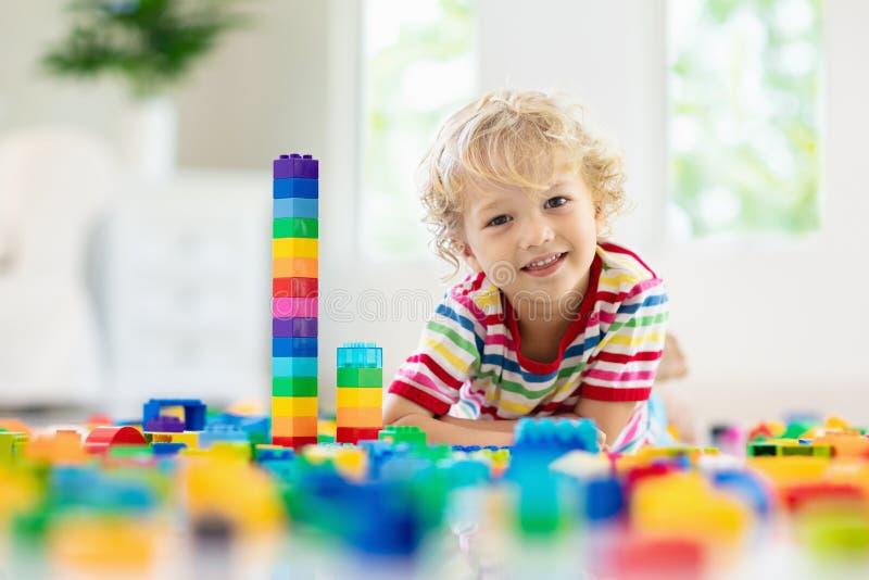 Ni?o que juega con los bloques del juguete Juguetes para los cabritos fotos de archivo